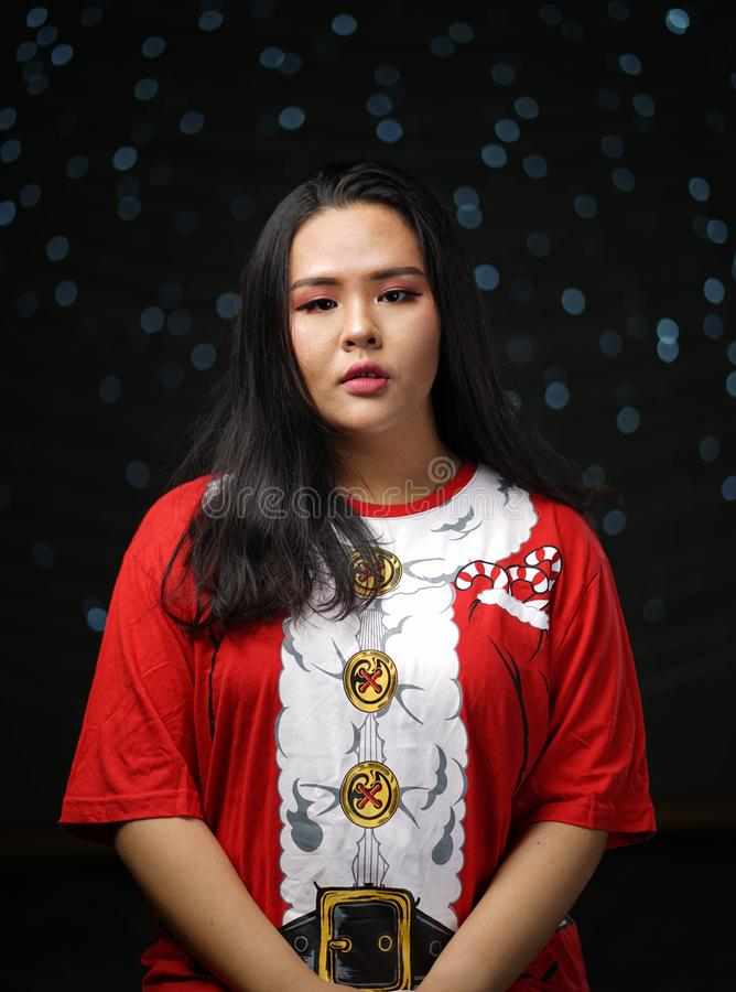 Asiatisk flicka som bär Santa Shirt Christmas Dark Glow Bokeh Backgro arkivfoto