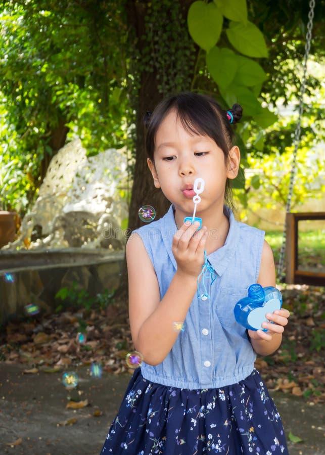 Asiatisk flicka som blåser bubblor Rolig aktivitet Naturligt agera gar royaltyfri fotografi