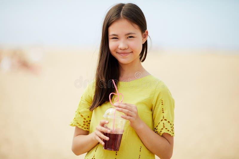 Asiatisk flicka som dricker den söta drycken arkivfoto