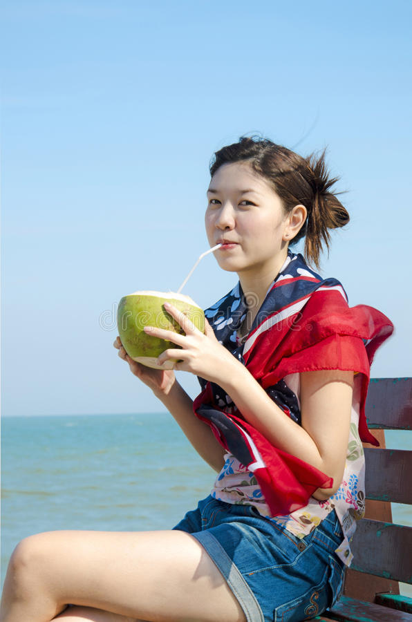 Asiatisk flicka som dricker kokosnötfrukt royaltyfria bilder