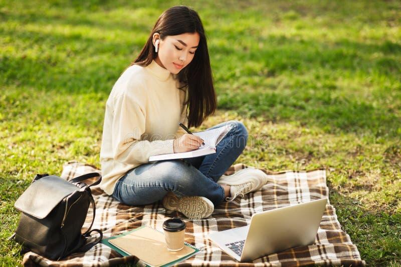 Asiatisk flicka som gör läxa, skriver anmärkningar och använder bärbara datorn arkivfoton