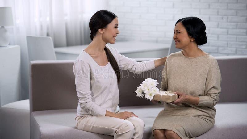 Asiatisk flicka som ger gåva till modern som firar årsdag av förbindelsen, familj arkivfoton