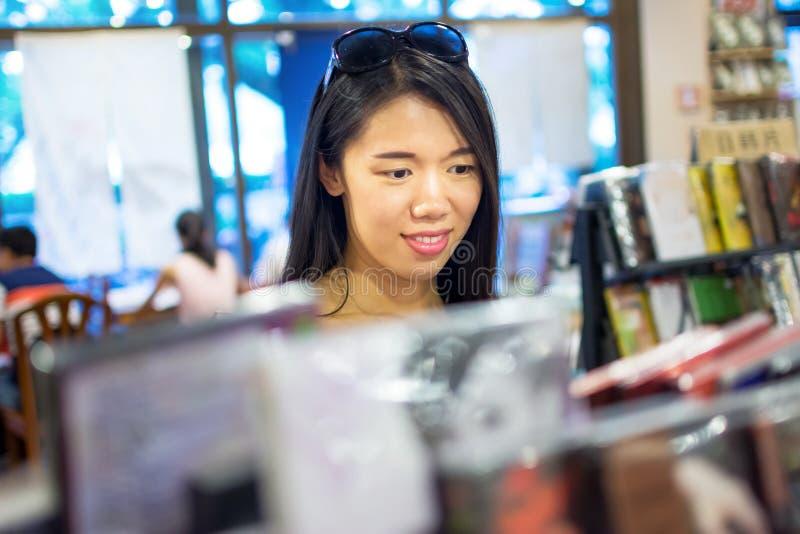 Asiatisk flicka som köper en CD-SKIVA royaltyfria bilder