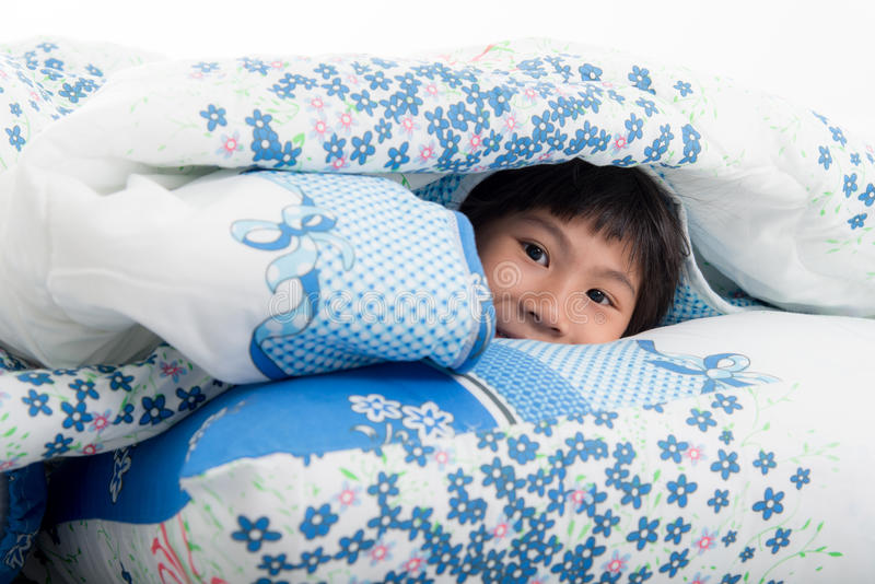 Asiatisk flicka som ligger under en filt i sängen arkivbild