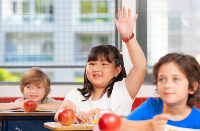 Asiatisk flicka som lyfter handen i mång- etniskt elementärt klassrum arkivfoton