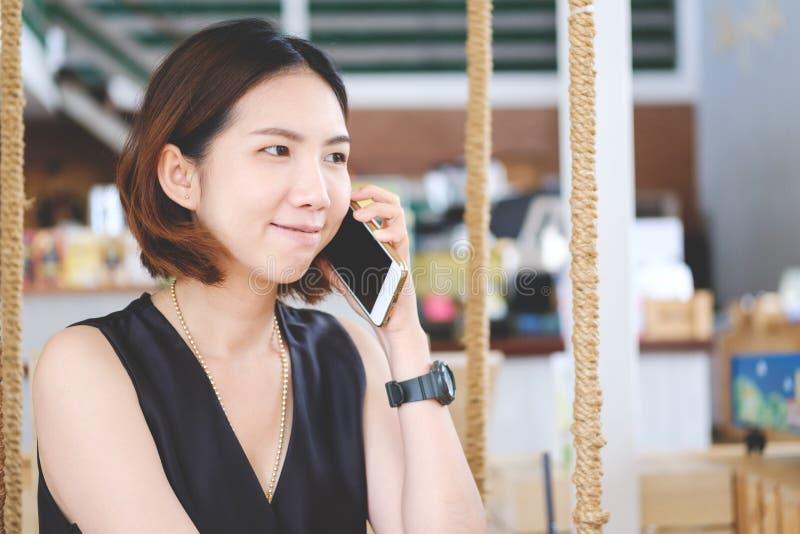 Asiatisk flicka som lyssnar till en appell på hennes mobiltelefon, ung beauti arkivfoto