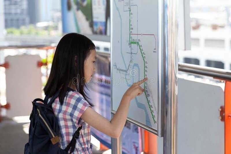 Asiatisk flicka som orienterar sig på kollektivtrafiköversikten, Stude royaltyfria foton