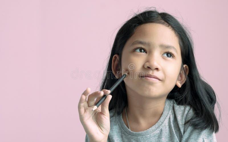 Asiatisk flicka som rymmer en blyertspenna och tänker något med rosa bakgrund royaltyfri foto