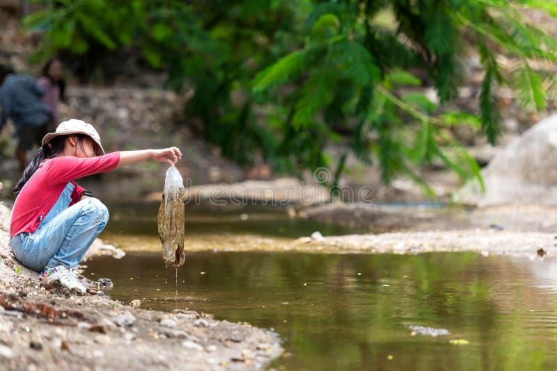 Asiatisk flicka som samlar avskräde och plast- på floden till dumpat in i avfallet royaltyfri fotografi