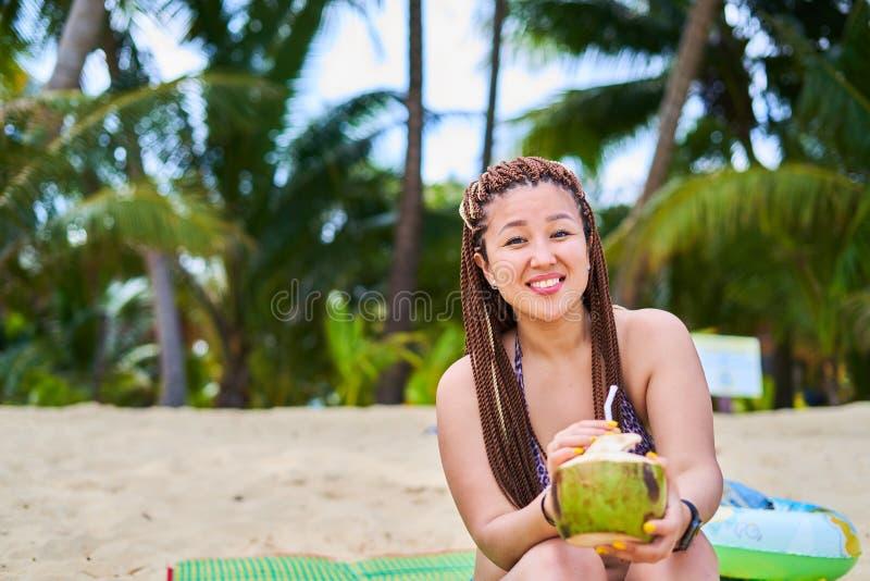 Asiatisk flicka som sitter av havet som ler och rymmer en kokosnöt fotografering för bildbyråer
