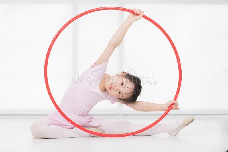 Asiatisk flicka som sitter och rymmer det gymnastiska beslaget royaltyfri foto