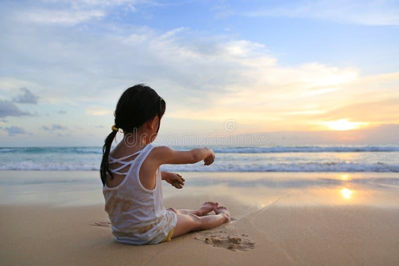 Asiatisk flicka som sitter och spelar sand på stranden på solnedgången arkivbilder