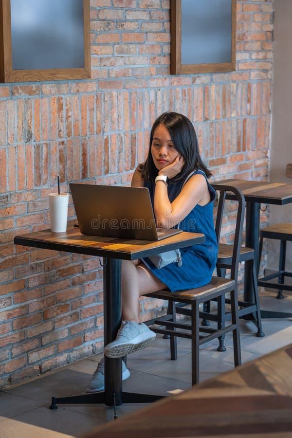 Asiatisk flicka som sitter på kaffetabellen och använder bärbara datorn royaltyfri fotografi