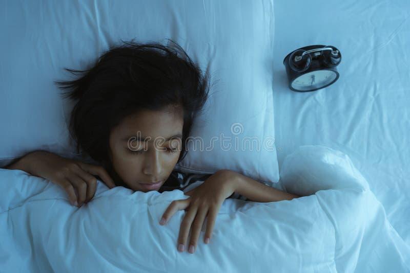 Asiatisk flicka som sover på sängen på midnatt Inom sovrummet är djup sömn för mörk liten flicka arkivfoton