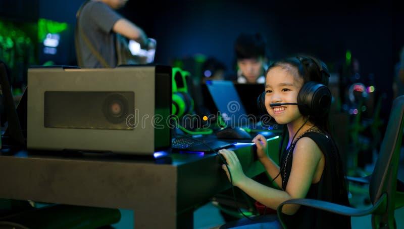 Asiatisk flicka som spelar dataspelar i internetkafé royaltyfri foto