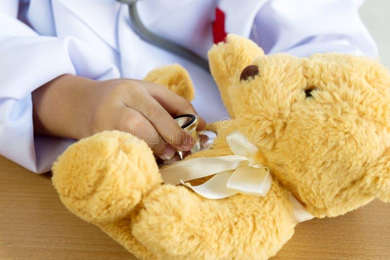 Asiatisk flicka som spelar som en docka för doktorsomsorgbjörn arkivfoto