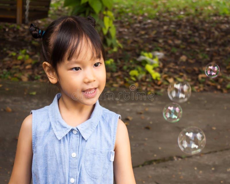 Asiatisk flicka som spelar med att blåsa bubblor Rolig aktivitet Natura royaltyfria foton