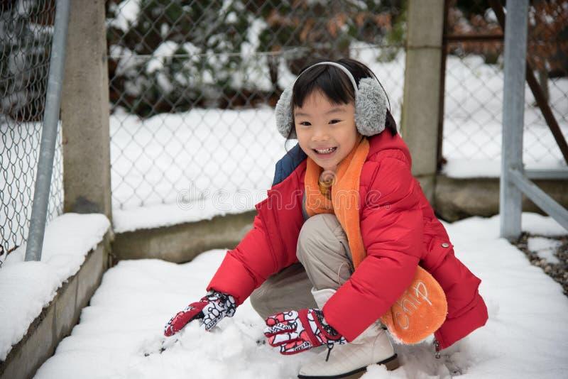 Asiatisk flicka som spelar med insnöade Schweiz, Europa royaltyfri foto