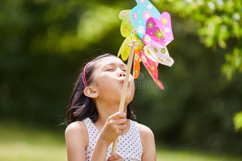 Asiatisk flicka som spelar med väderkvarnen royaltyfri fotografi