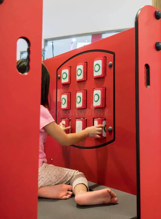 Asiatisk flicka som spelar muskelryckningen Tac Toe som matchar panelen på lekplatsen arkivfoto