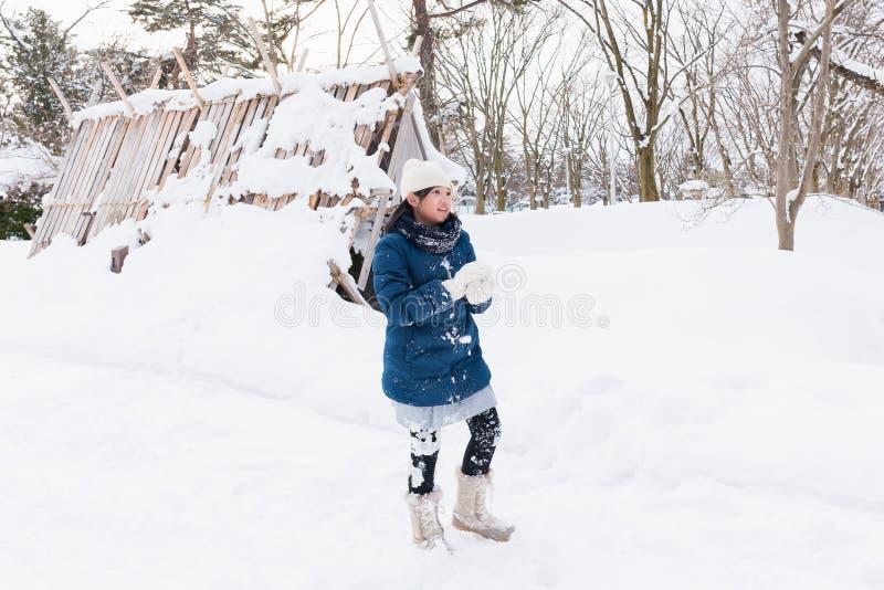 Asiatisk flicka som spelar snö royaltyfri foto