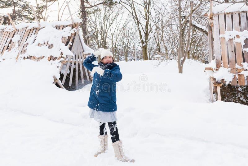 Asiatisk flicka som spelar snö arkivbild