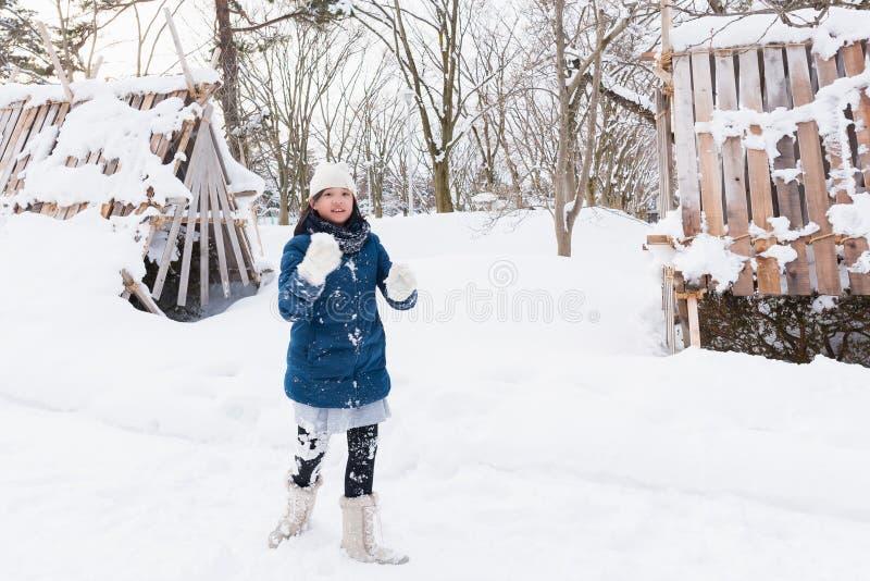 Asiatisk flicka som spelar snö arkivfoton