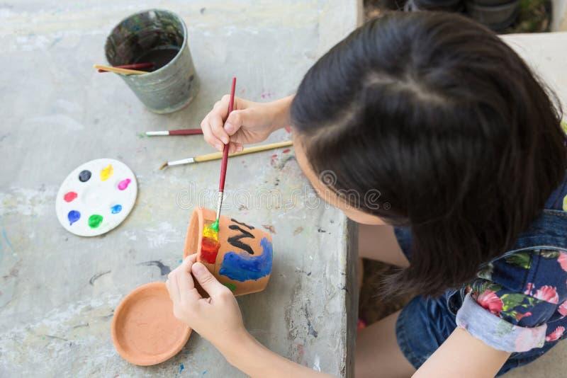 Asiatisk flicka som studerar och l?r konsten, ungen som anv?nder m?larpenseln till att m?la vattenf?rg p? den inlagda v?xten som  royaltyfria bilder