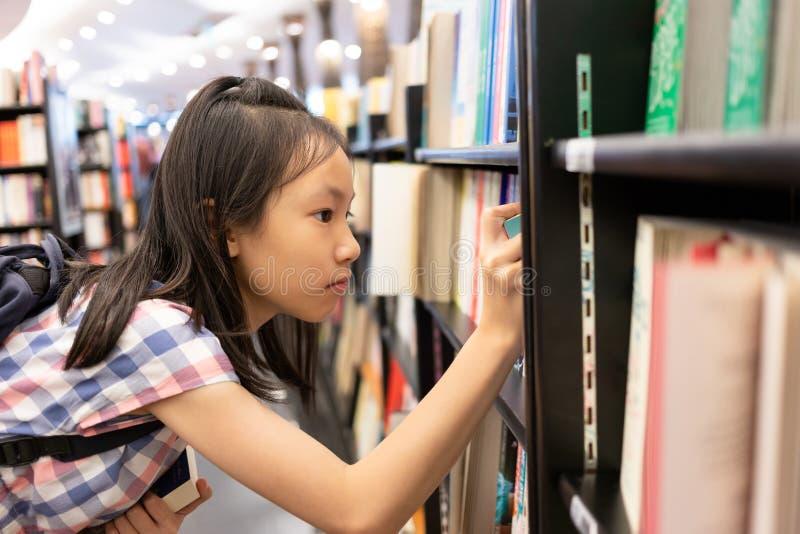 Asiatisk flicka som väljer boken från en bokhylla i arkivet, läs- Co royaltyfria foton
