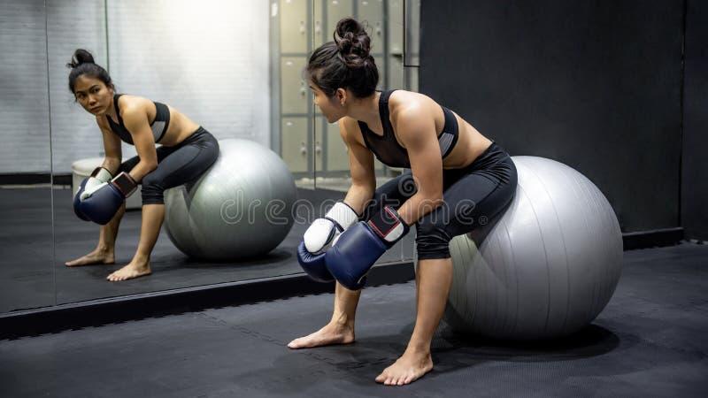 Asiatisk flickaboxare som sitter p? ?vningsboll i idrottshall royaltyfri bild