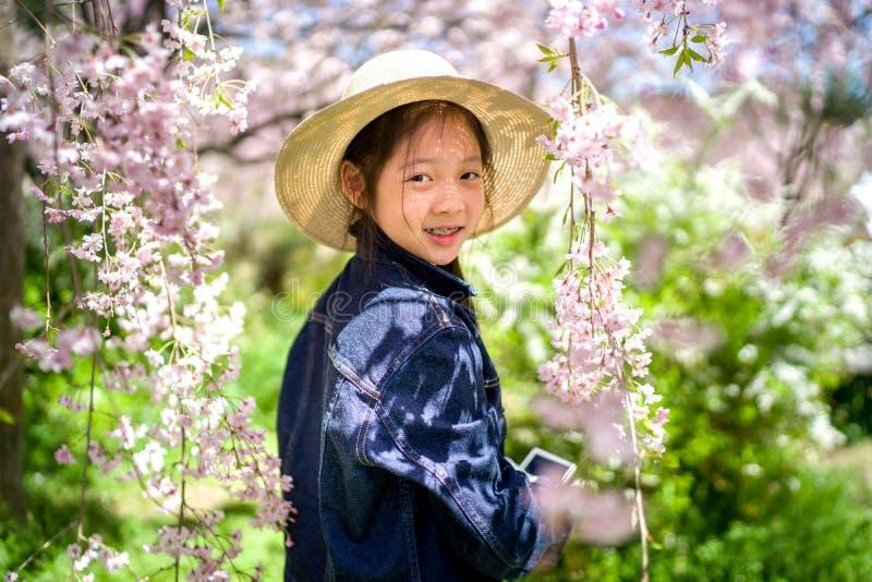 Asiatisk flickainnehavkamera som tar fotoet på att resa tur under semester arkivfoton