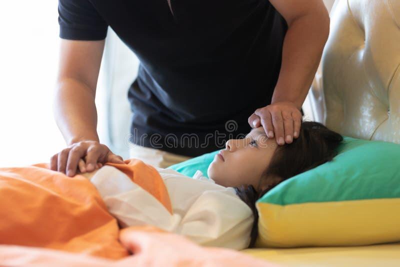 Asiatisk flickakänsla som är sjuk som är kvinnlig ha huvudvärk och hög temperat arkivfoto