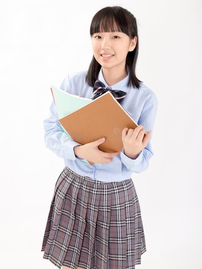 Asiatisk flickastudent i skolalikformig fotografering för bildbyråer