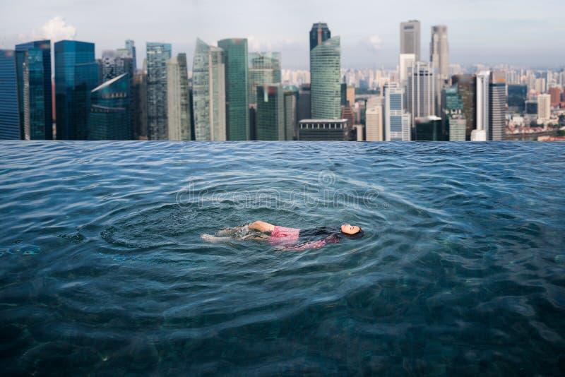 Asiatisk flickaswimimg i taköverkantsimbassängen i hotell arkivfoton