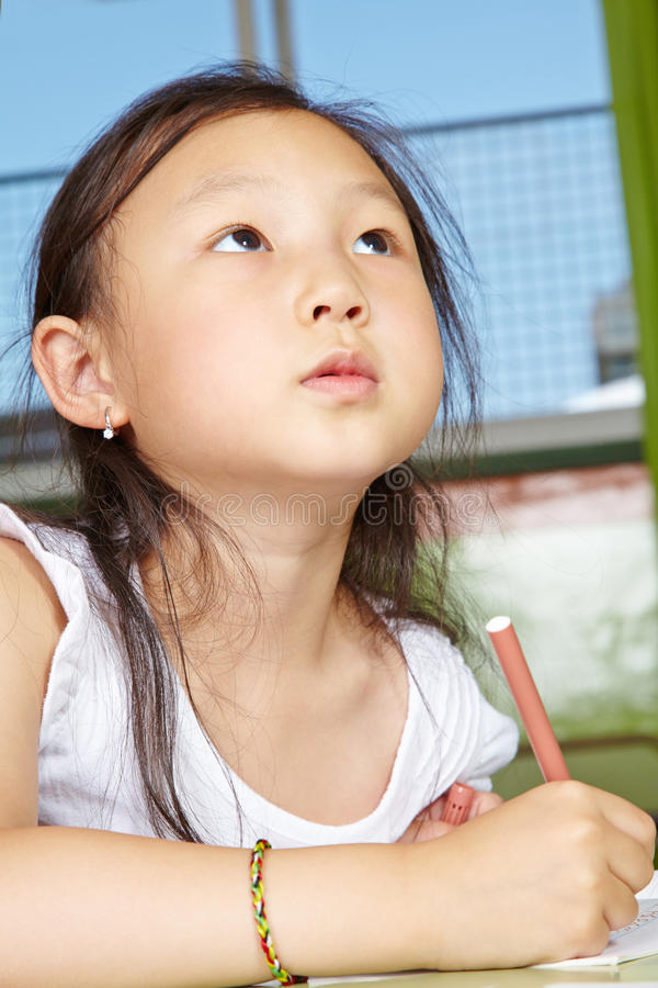 Asiatisk flickateckning i dagis royaltyfri fotografi