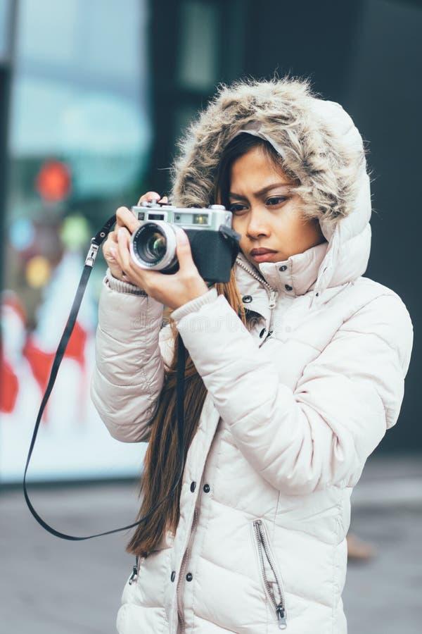 Asiatisk fotograf för Freelancer som undersöker i kallt väder royaltyfri fotografi