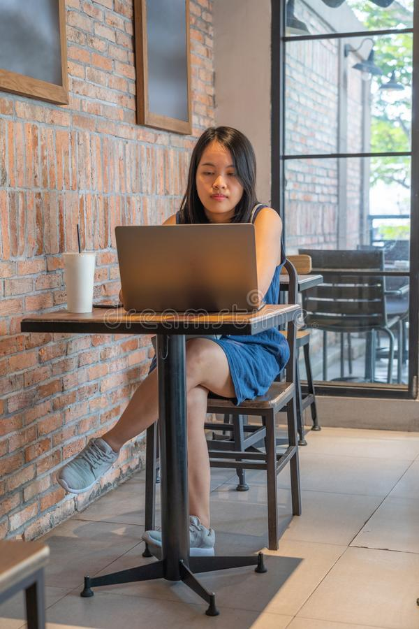 Asiatisk freelancer som arbetar på bärbara datorn på den lantliga coffee shop arkivfoton