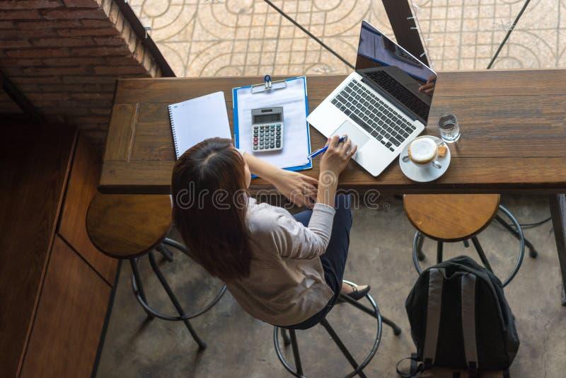 Asiatisk freelancer som arbetar på bärbara datorn på kafét fotografering för bildbyråer