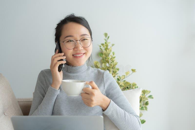 Asiatisk funktionsduglig kvinna på hennes framsidakläderexponeringsglas, leende, samtal på telefonen Den unga affärskvinnan drick arkivfoton