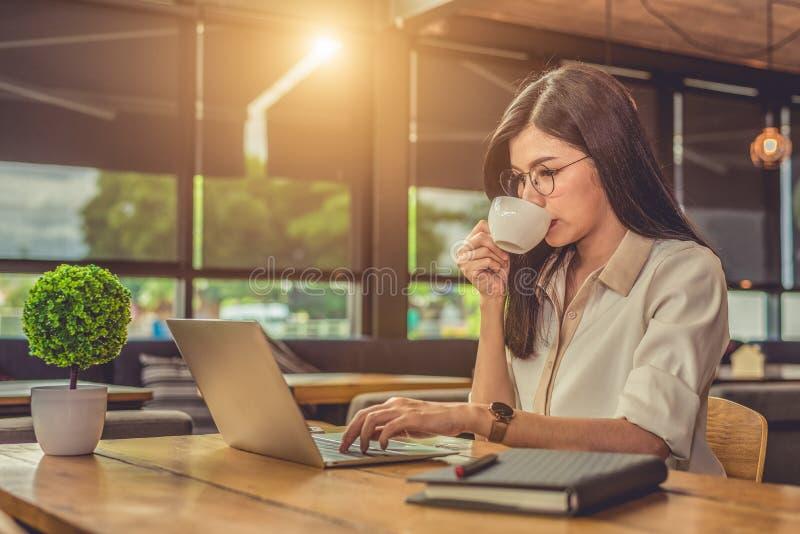 Asiatisk funktionsduglig kvinna som anv?nder b?rbara datorn och dricker kaffe i kaf? Folk och livsstilbegrepp Teknologi- och aff? royaltyfri fotografi
