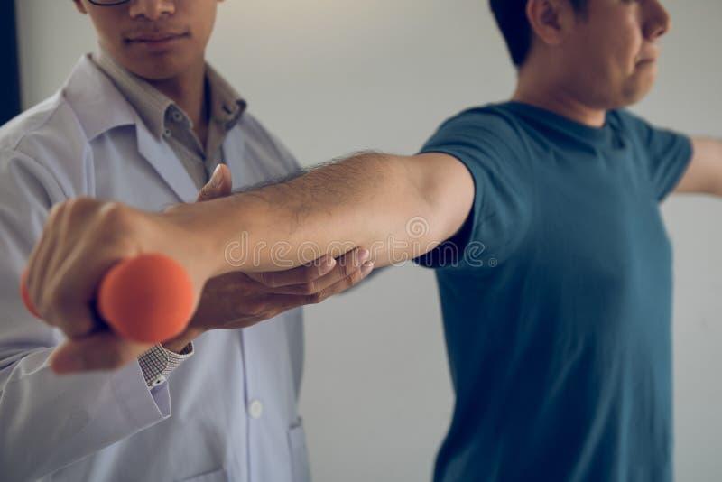 Asiatisk fysioterapeut, hjälpande som lyftande hantlar för en patient arbetar till och med hans återställning med vikter i klinik arkivbild
