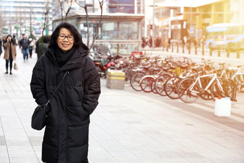 Asiatisk gammal dam som bär en tröjaöverrocksvart royaltyfri fotografi