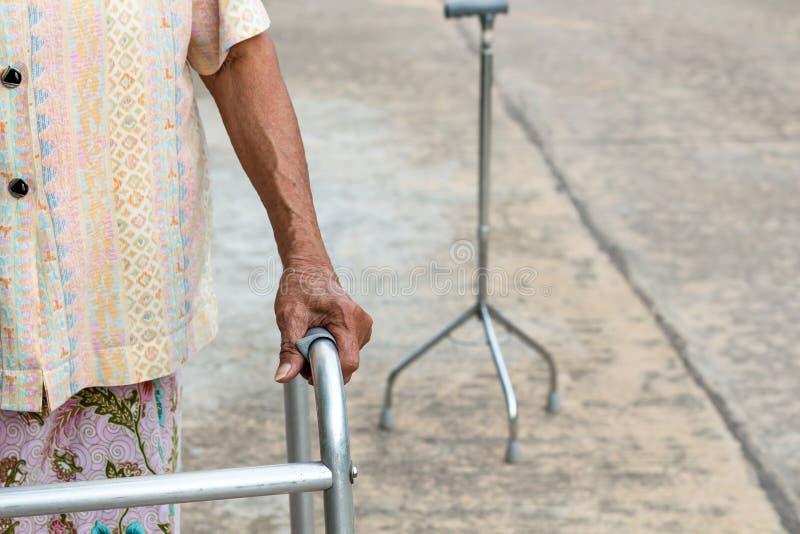 Asiatisk gammal kvinna för The†‹som står med hans händer på en gå pinne, hand av den gamla kvinnan som rymmer en personalrottin royaltyfria bilder