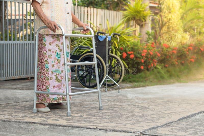 Asiatisk gammal kvinna för The†‹som står med hans händer på en gå pinne, hand av den gamla kvinnan som rymmer en personalrottin royaltyfria foton