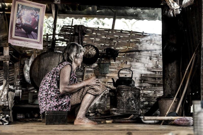 Asiatisk gammal kvinna i kök arkivfoto