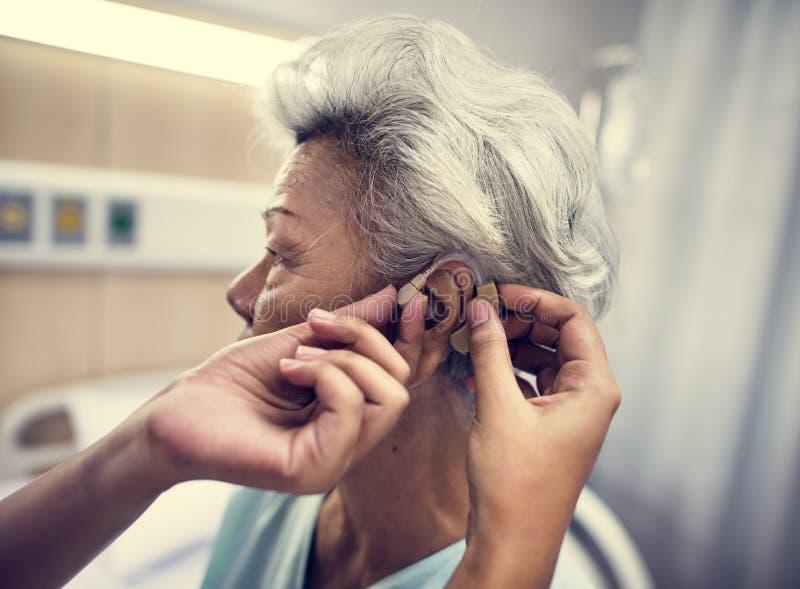 Asiatisk gammal kvinna som har henne kontrollerade öron royaltyfri foto