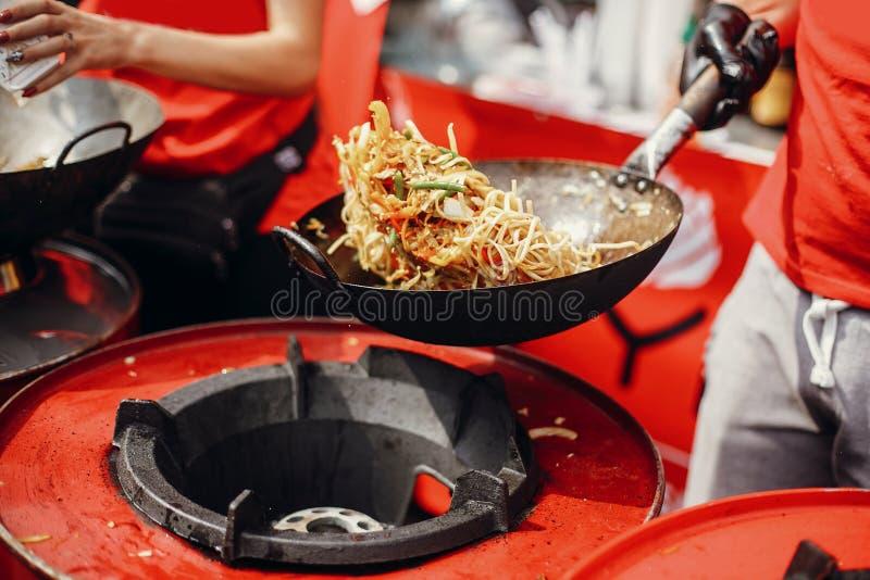 Asiatisk gatamatfestival i stad Kock som lagar mat nudlar och grönsaker i en panna på brand Stekte kinesiska japanska nudlar med arkivbilder