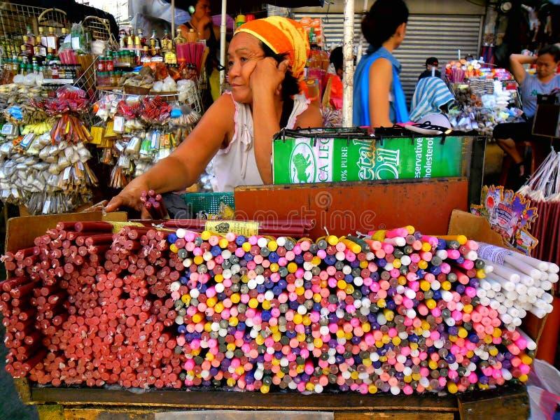 Asiatisk gatuförsäljare som förutom säljer den färgade quiapokyrkan för stearinljus i quiapoen, manila, philippines i asia arkivbild