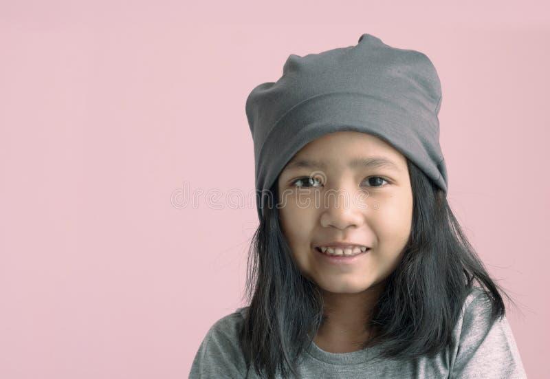 Asiatisk grillycka för stående och le på rosa bakgrund med kopieringsutrymme royaltyfria foton