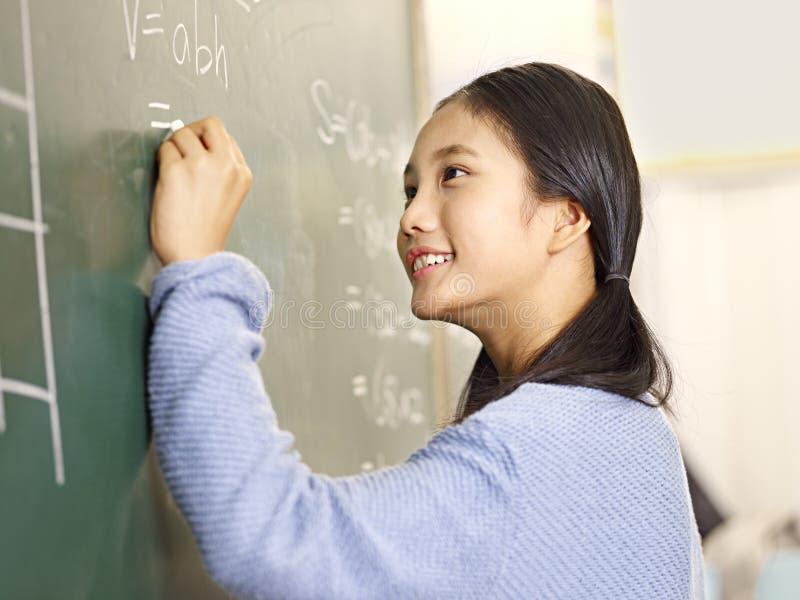 Asiatisk grundskolastudent som löser ett matematikproblem fotografering för bildbyråer